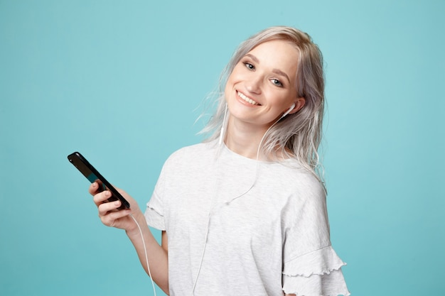 Persona de sexo femenino feliz con auriculares y teléfono escuchando música en el estudio.