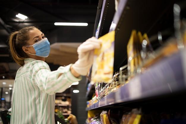 Persona de sexo femenino con máscara y guantes comprando alimentos en el supermercado