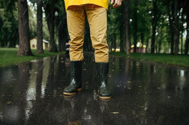 Persona del sexo masculino en capa de lluvia y botas de goma, clima húmedo en el callejón. el hombre posa en el parque de verano en día lluvioso. protección contra el agua, gotas