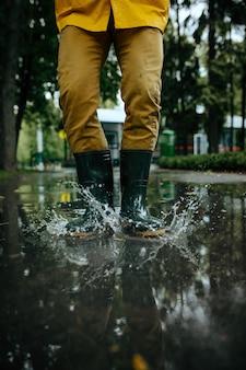 Persona del sexo masculino en capa de lluvia y botas de goma saltando en charcos, clima húmedo en el callejón. el hombre posa en el parque de verano, día lluvioso. protección contra el agua, gotas
