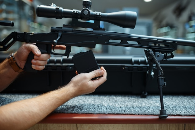 Persona del sexo masculino carga rifle de francotirador en la armería. equipo para cazadores en stand en almacén de armas, pasatiempo de caza y tiro deportivo