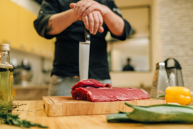 Persona del sexo masculino con cuchillo y trozo de carne cruda sobre tabla de madera