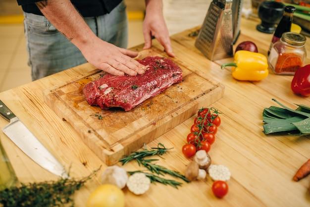 Persona del sexo masculino manos condimento pedazo de carne cruda sobre tabla de madera