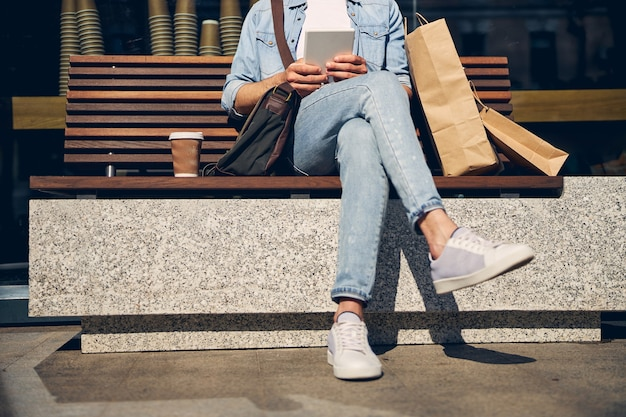 Persona del sexo masculino relajado sentado en el banco y respondiendo al mensaje de ingresos, descansando después de ir de compras