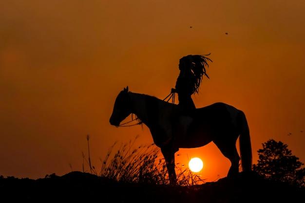 Persona de silueta a caballo al atardecer
