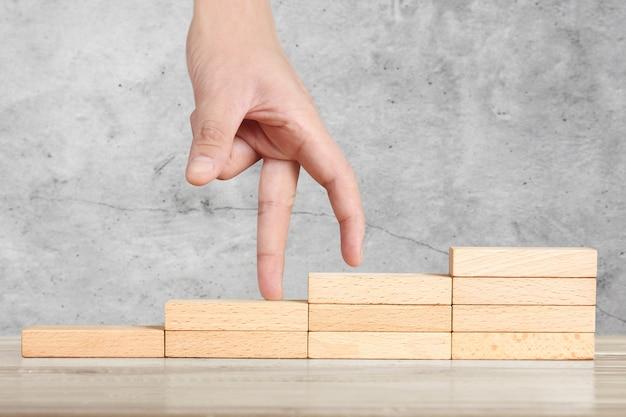 Persona similar a la mano intensificando el apilamiento de bloques de madera como escalón