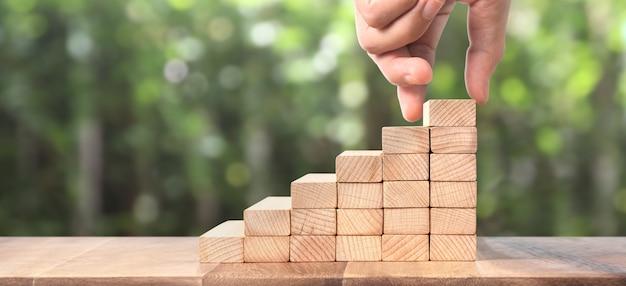 Persona similar a mano intensificando escalera de juguete madera