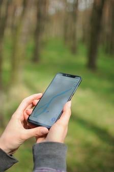 La persona sola está buscando un camino a través del navegador gps en el teléfono inteligente en el bosque