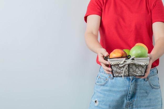 Una persona sosteniendo una canasta de frutas en la mano.