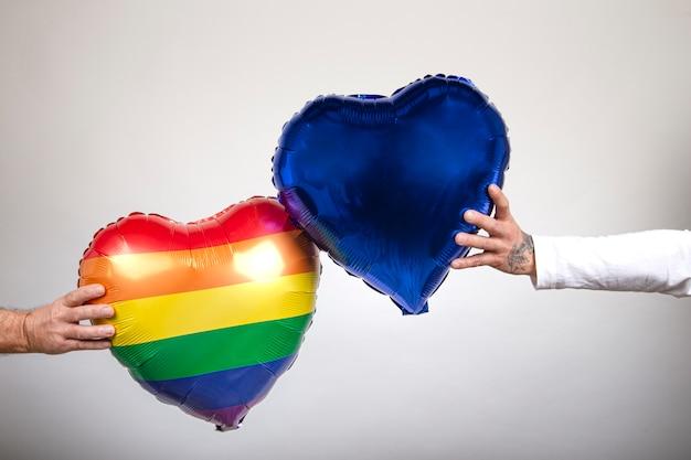 Persona sosteniendo dos globos en forma de corazón