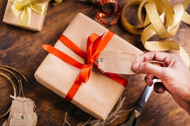 Persona sosteniendo la etiqueta encima de la caja de regalo