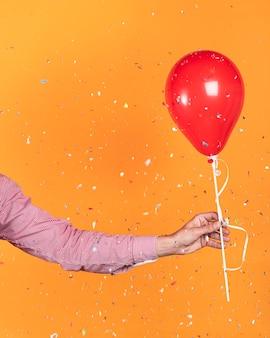 Persona sosteniendo un globo rojo y confeti