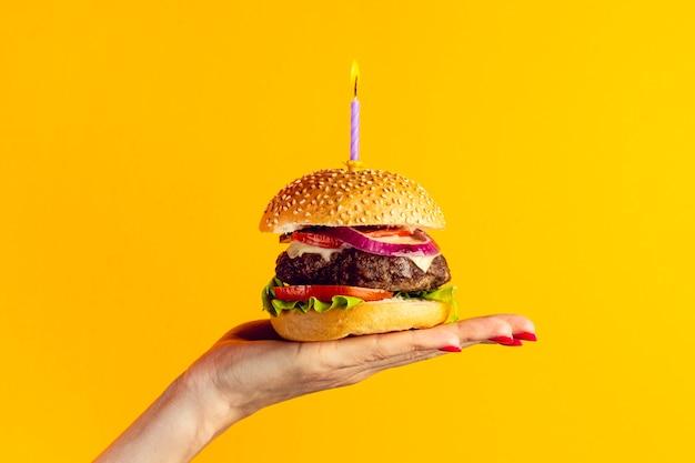 Persona sosteniendo una hamburguesa de aniversario
