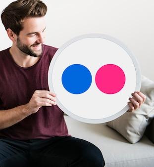 Persona sosteniendo un ícono de flickr