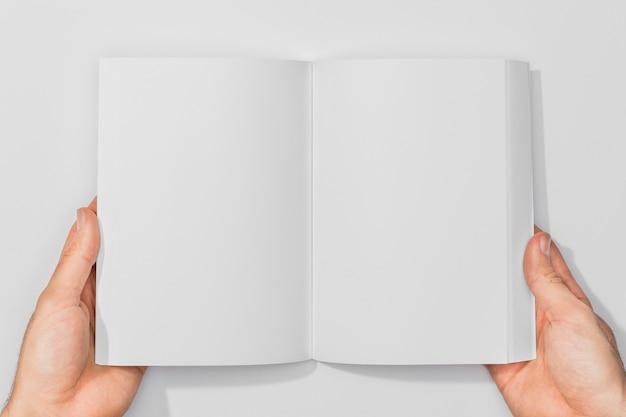 Persona sosteniendo un libro de espacio de copia