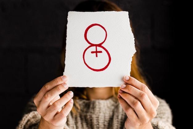 Persona sosteniendo un papel para el día de la mujer.