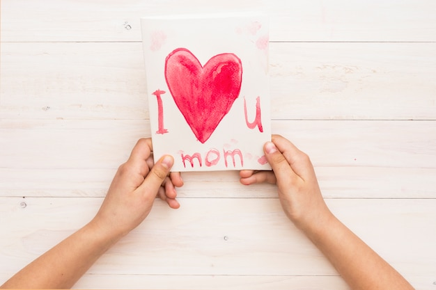 Persona sosteniendo papel con te amo inscripción mamá
