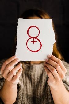 Persona sosteniendo un papel para la vista frontal del día de la mujer