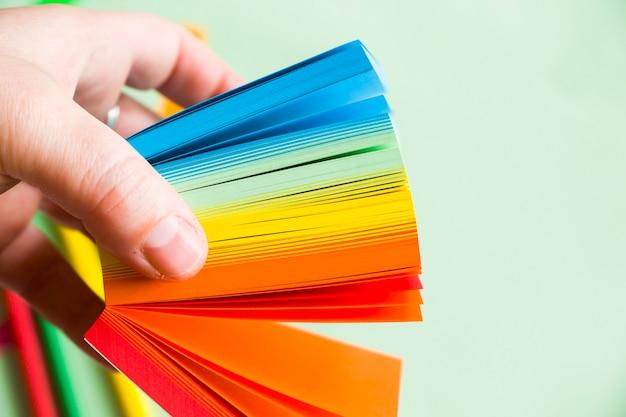 Persona sosteniendo papeles de colores