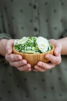 Persona sosteniendo un plato de ensalada de cebollas deshidratadas