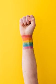 Persona sosteniendo el puño con la bandera del arco iris en la muñeca
