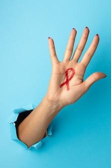 Persona sosteniendo un símbolo rojo del día mundial del sida