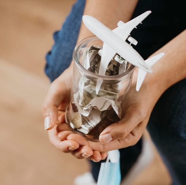 Persona sosteniendo tarro transparente con dinero y figurilla de avión