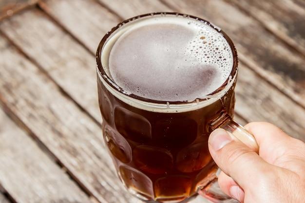 Persona sosteniendo un vaso de cerveza fría con una superficie de madera