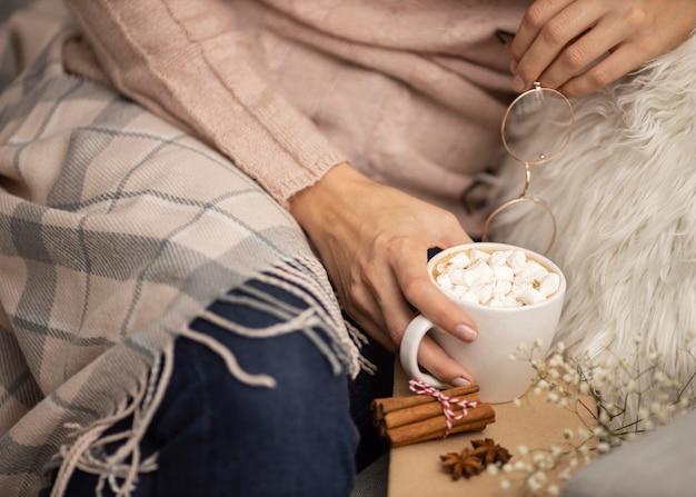 Persona sosteniendo vasos y taza de chocolate caliente con malvaviscos