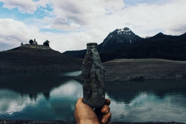 Persona sosteniendo una vieja botella de vidrio cubierta de barro cerca del agua con montañas