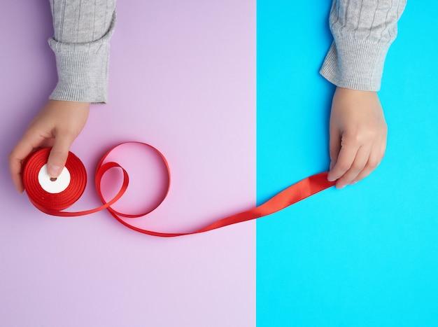 Persona sujetando una canilla con una cinta de seda roja