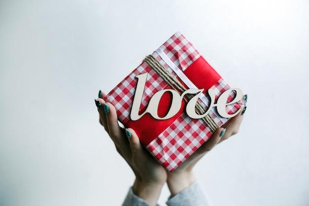 Persona sujetando regalo rojo con palabra