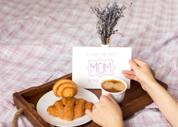 Persona con tarjeta de felicitación y taza de café en bandeja