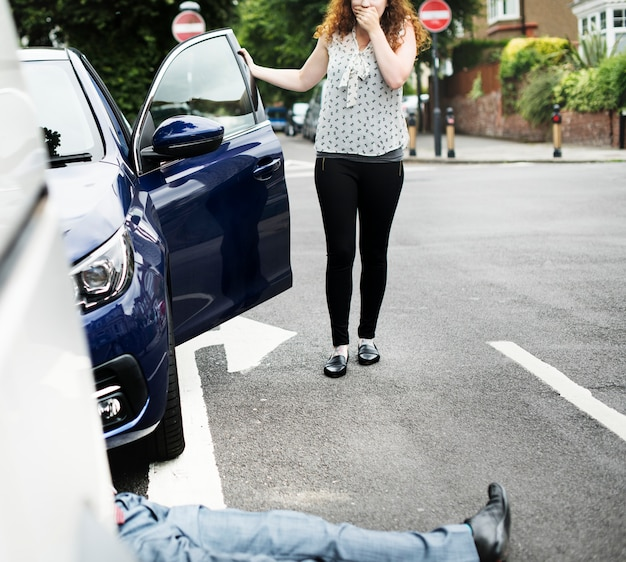 Persona tendida en el suelo después de un accidente automovilístico.