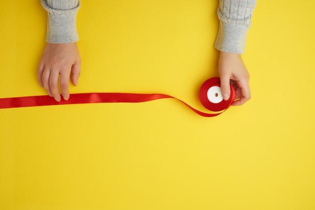 Persona tiene cinta roja sobre una superficie amarilla