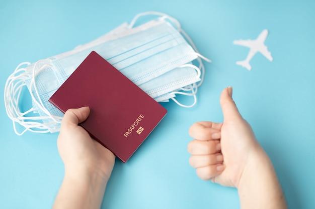 Persona titular de un pasaporte con mascarillas quirúrgicas sobre un fondo azul.