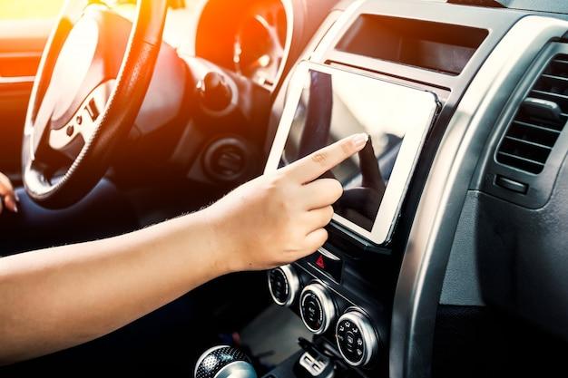 Persona tocando una tablet mientras conduce