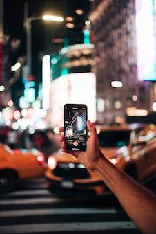 Persona tomando una foto con una ciudad vívida