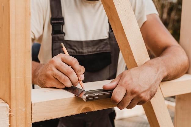 Persona tomando medidas sobre madera