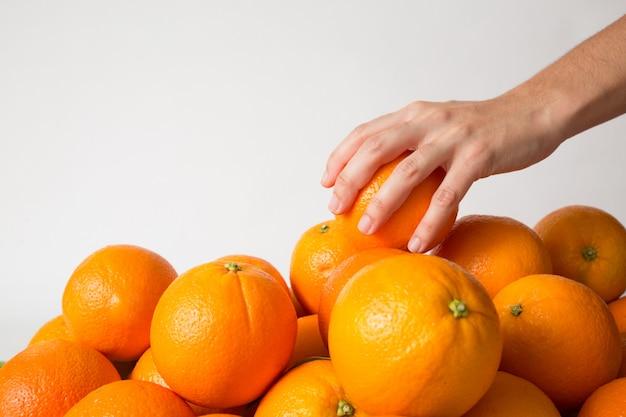 Persona tomando naranja del montón de frutas