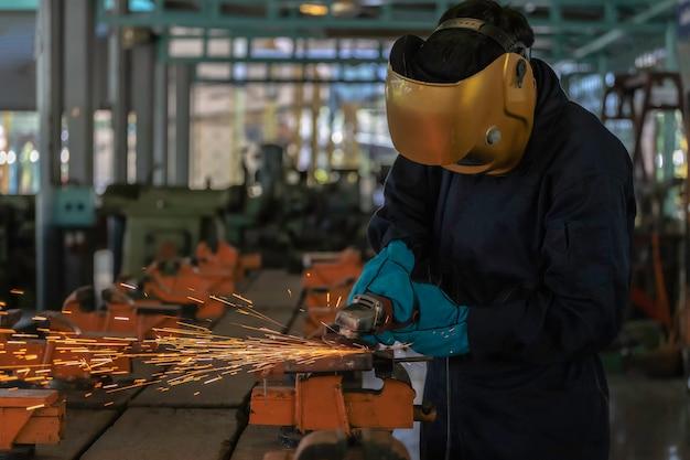 Persona trabajadora acerca del soldador de acero uso de la máquina de soldadura eléctrica.