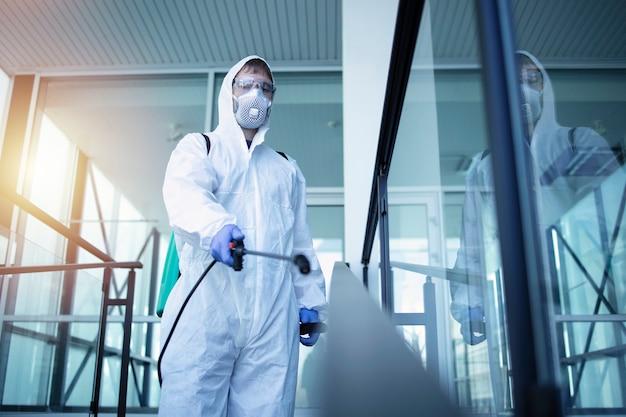 Persona con traje blanco de protección química que realiza la desinfección de áreas públicas para detener la propagación del virus corona altamente contagioso