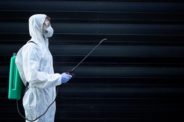 Persona con traje blanco de protección química sosteniendo un rociador con productos químicos desinfectantes para detener la propagación de virus altamente contagiosos