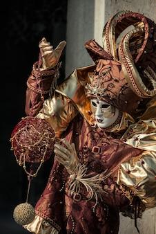 Persona en traje de carnaval veneciano juega con bola decorativa