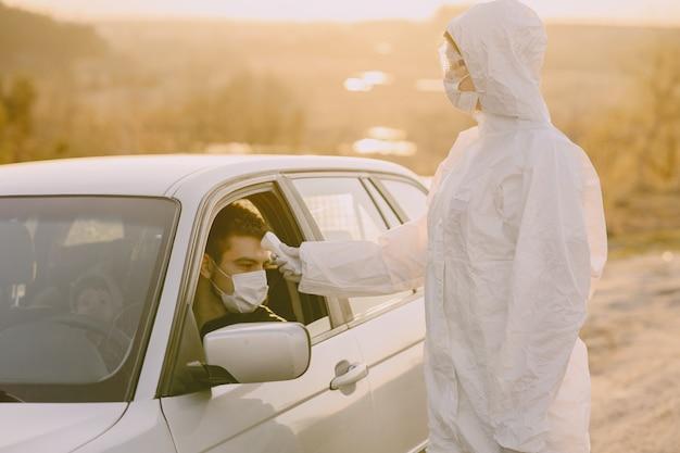 Persona en traje de protección verifica la temperatura