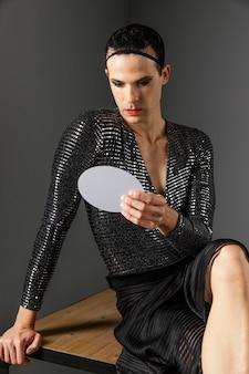 Persona transgénero joven mirando en el espejo