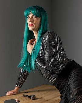 Persona transgénero joven con peluca verde mirando a otro lado