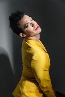 Persona transgénero vestida con chaqueta amarilla y lápiz labial rojo