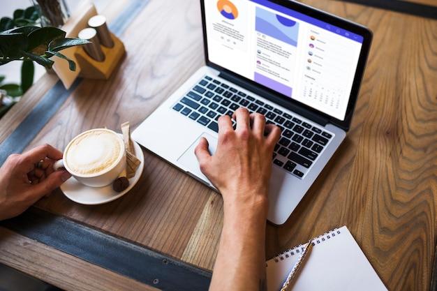 Persona usando laptop en cafe