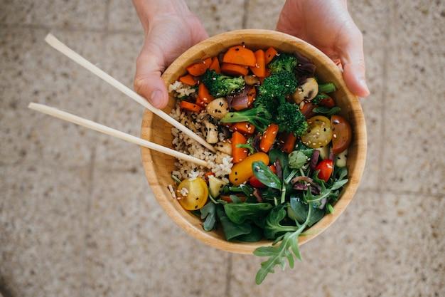La persona vegana sostiene un tazón de madera de buda de coco lleno de verduras saludables, verduras, granos y palillos.